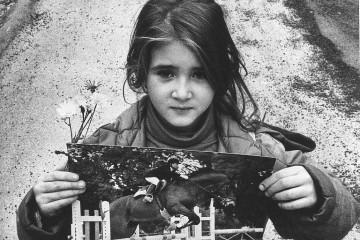 """Una bambina mostra la foto di Giuseppe di Matteo, figlio del pentito Santino, ucciso il 23 novembre """"93 a soli 13 anni. Fonte: archivioantimafia.org"""